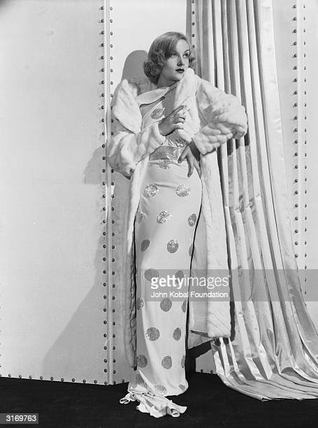 American film actress Carole Lombard wearing a spotted white dress and a fur coat