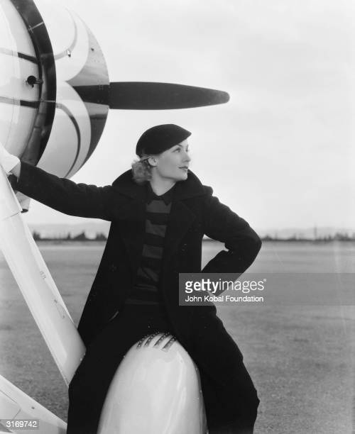 American film actress Carole Lombard wearing a trouser suit and leaning on the side of an aircraft