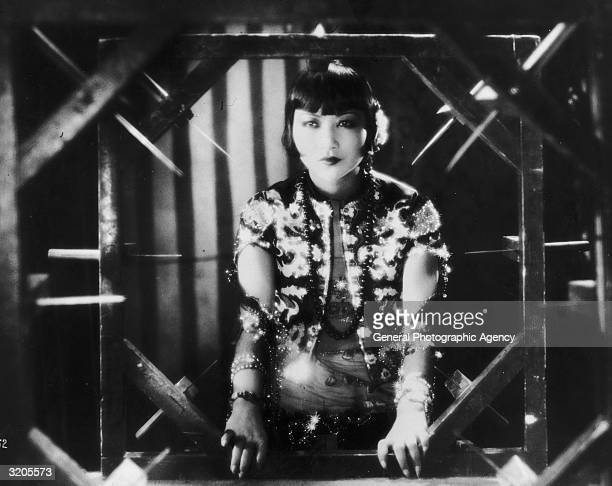 American film star Anna May Wong framed by a sinisterlooking contraption in a still from one of her films