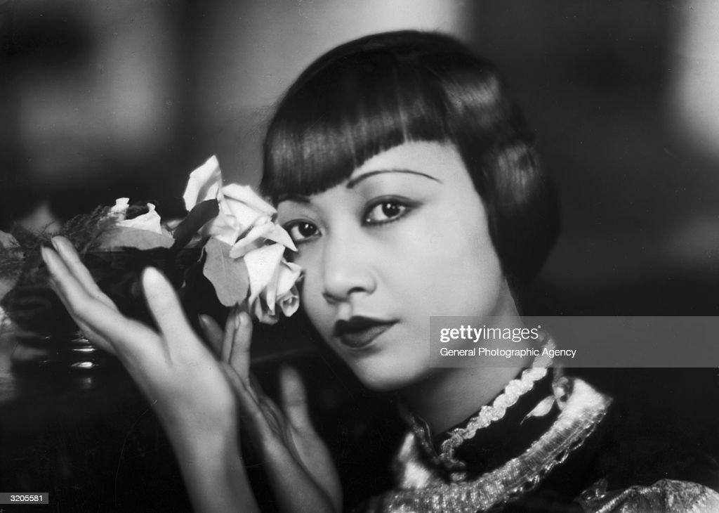 American film star, Anna May Wong (1905 - 1961) poses with a cut rose.