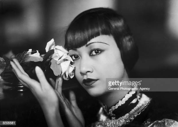 American film star Anna May Wong poses with a cut rose