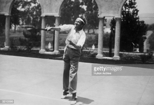 American film star Edmund Lowe playing tennis