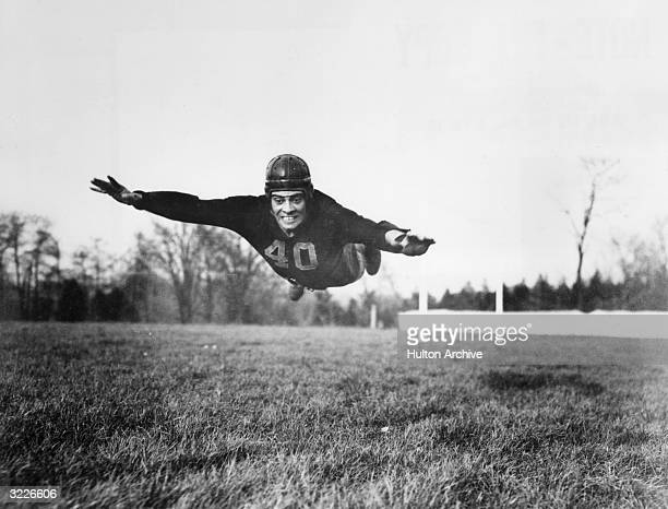 American football player Vince Lombardi wearing a Fordham University uniform and a helmet diving into the air outdoors in a field
