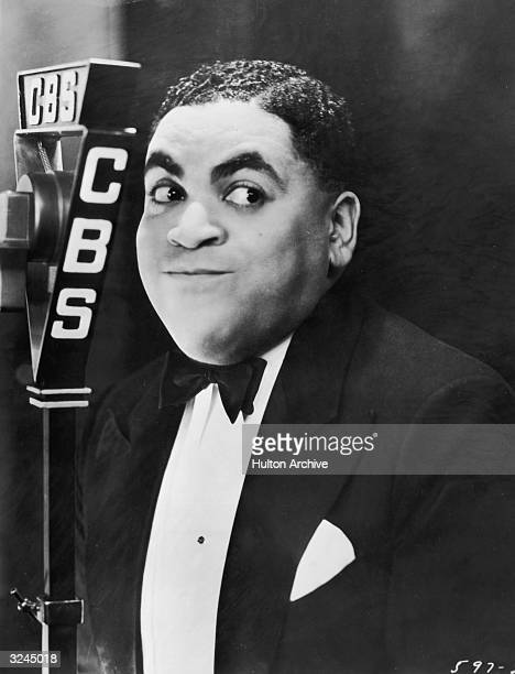 American jazz musician Fats Waller smiles in front of a CBS radio microphone