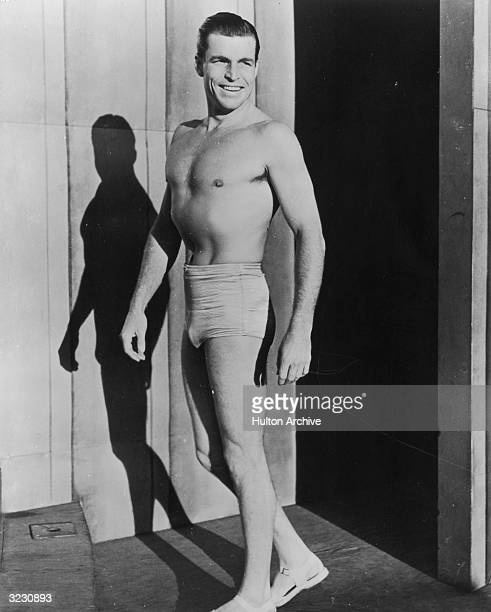 American Olympic swimming champion turned film actor Buster Crabbe wearing swimming trunks and sandals