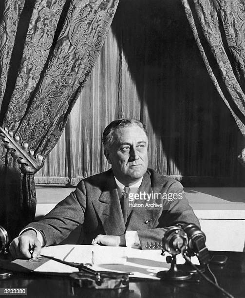 American President Franklin Roosevelt sits at a desk with microphones probably during a radio broadcast