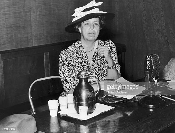 American social reformer Eleanor Roosevelt sits at a desk in front of a microphone as guest host of the NBC radio program 'Hobby Lobby'
