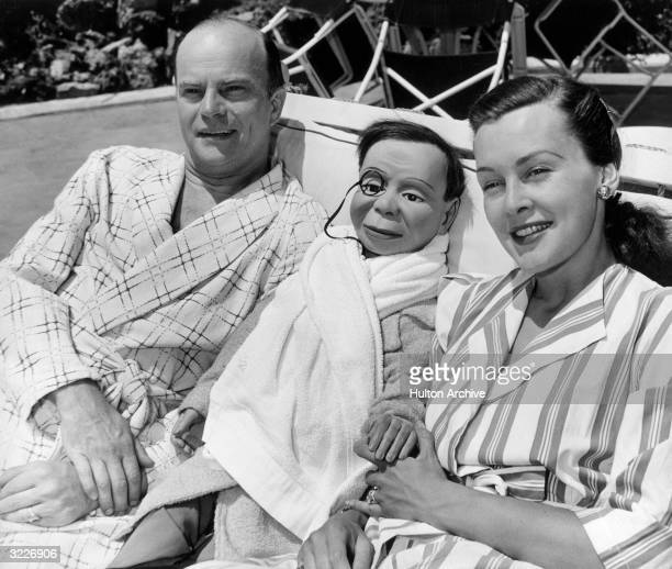 American ventriloquist Edgar Bergen and his wife American actor Frances Bergen reclining on a pool chair with Bergen's dummy Charlie McCarthy All...