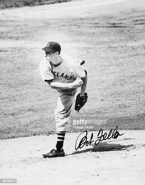 Autographed photograph of American baseball player Bob Feller, pitcher for the Cleveland Indians, pitching on a mound.