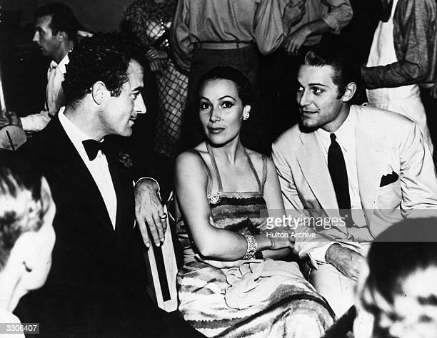 Dolores Del Rio Hollywood film star and wife of MGM's Art Director Cedric Gibbons sitting between Gilbert Roland and Jon Hall at the West Side Tennis...