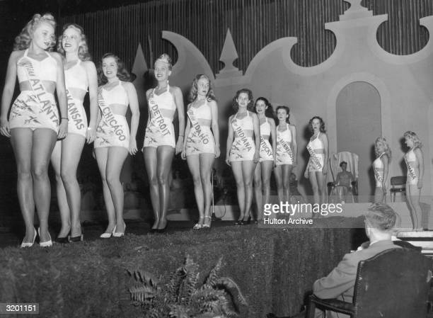 Eleven of the fifteen remaining finalists in the Miss America pageant parade across the stage in front of a panel of judges during the swimsuit...