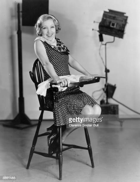 English actress Bessie Love sitting in a humansized baby highchair in a photography studio