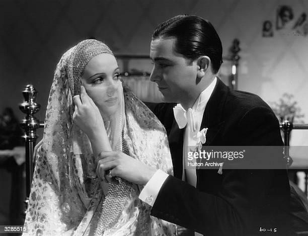 English actress Jessie Matthews draws a veil across her face as she casts an alluring glance at a smitten Robert Young in the film 'Head Over Heels'