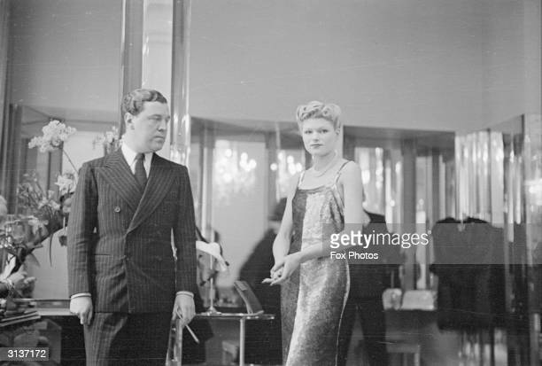English fashion designer Norman Hartnell looking critically at a model wearing one of his designs.