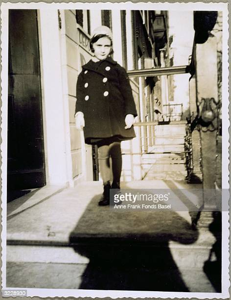 EXCLUSIVE A fulllength portrait of Anne Frank wearing a coat hat and gloves standing on the doorstep of her father's first office in the Singel...