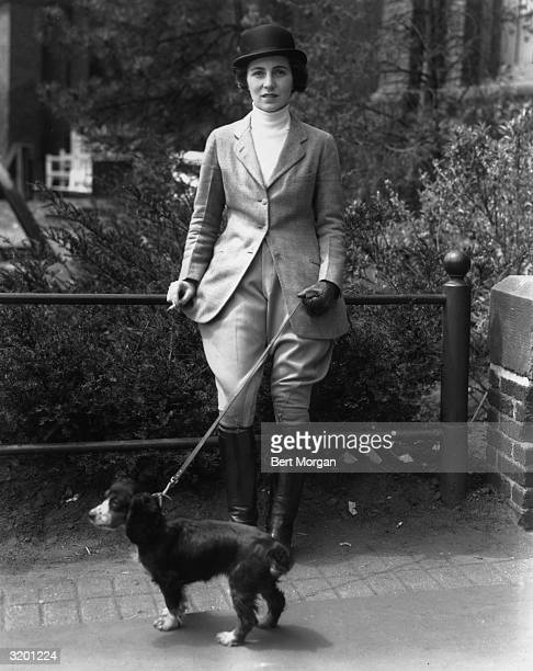EXCLUSIVE Fulllength view of Mrs John V Bouvier III wearing a riding habit smoking a cigarette while holding her spaniel 'Bonnett' on a leash at a...
