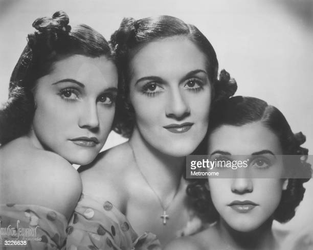 EXCLUSIVE Portrait of the Andrews Sisters posing head to head in offtheshoulder gowns LR Maxene LaVerne and Patty