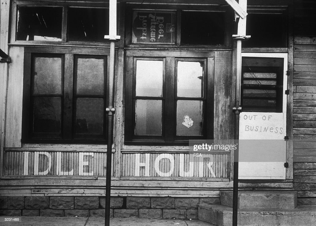 Exterior view of a pub called Idle Hour, in front of which hangs an 'OUT OF BUSINESS' sign, during the Great Depression, United States.