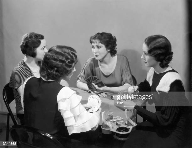 Four women in dresses play cards at a table with drink holders One woman holds a cigarette and rests her hand on a scorepad
