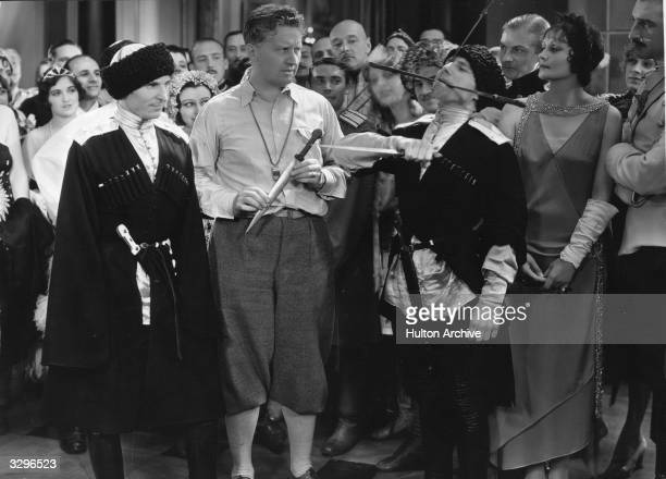 Fred Niblo is directing Greta Garbo for her MGM picture 'War In The Dark' and she gets some expert instruction in the use of knives from a Cossack...