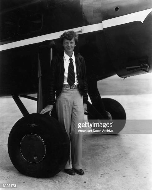 Fulllength image of American aviator Amelia Earhart the first woman to complete a solo transatlantic flight posing near the wheels of her airplane in...