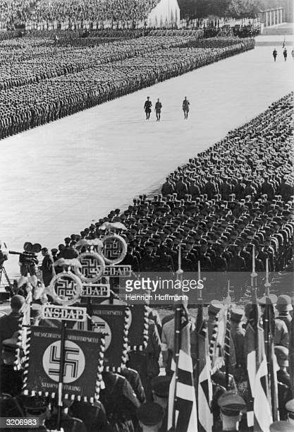 Fulllength image of Nazi troops standing in military formations while top Nazi officials walk through a clearing in the crowded stadium during an...