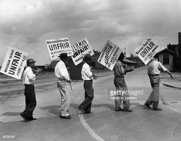 Fulllength image of workers from various unions carrying signs protesting Waterman Repair Division on a street outside of company property Maryland