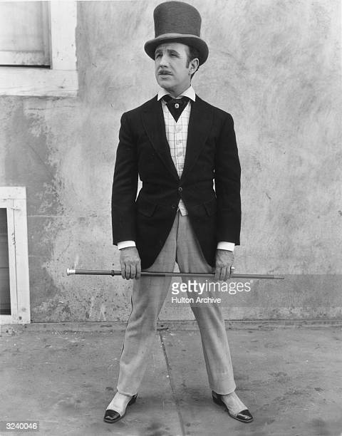 Fulllength portrait of a man standing with his legs apart while wearing a large top hat a cravat under a vest spats and holding a cane