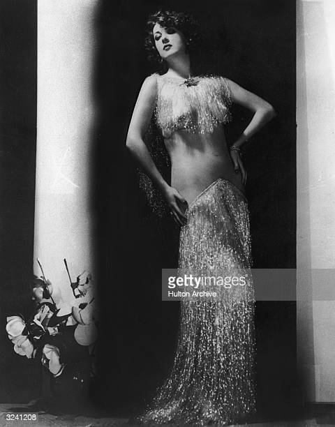 Fulllength portrait of American actor and stripper Gypsy Rose Lee dressed in a seethrough tinsel top and long tinsel skirt standing with her hands on...