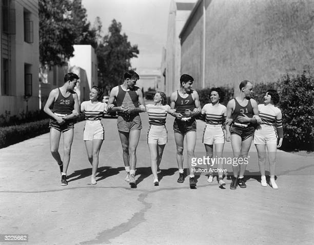 Fulllength portrait of members of the Motion Picture Studio All Stars Basketball Team the cast of Ray McCarey's short film 'Basketball' walking...