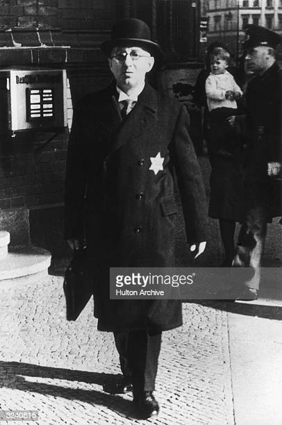 Fulllength view of a middle class German Jew walking with a briefcase in Berlin Nazi Germany He wears a Star of David on the overcoat of his business...