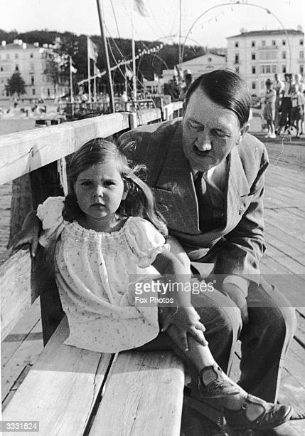 German dictator Adolf Hitler sitting on a bench with Helga Goebbels daughter of Nazi propagandist Paul Joseph Goebbels