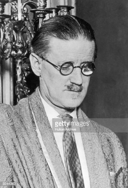 Headshot of Irish author James Joyce standing in front of a candelabra and looking down