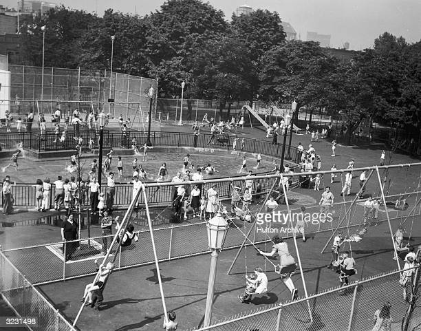 High angle view of children on the swings and playing in a wading pool at Bushwick Park Brooklyn New York City