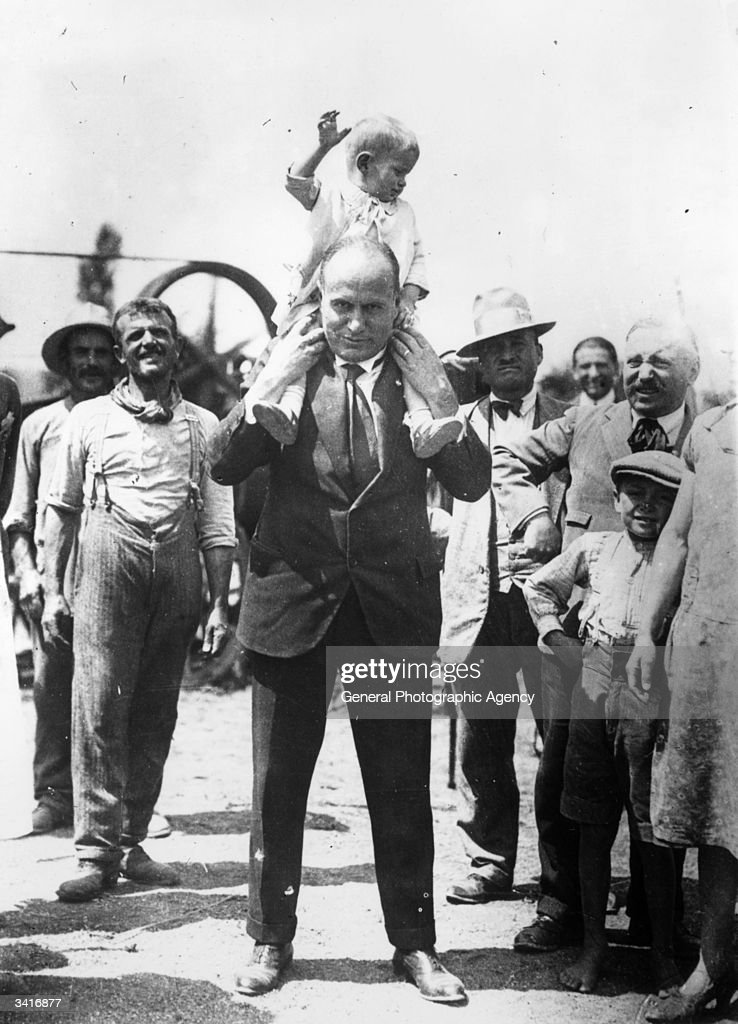 Italian dictator Benito Mussolini (1883 - 1945) with his youngest son Romano on his shoulders.