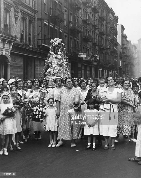 ItalianAmerican women and children carry a float through the street during a parade for St Rocco on Cherry Street Little Italy New York City The...
