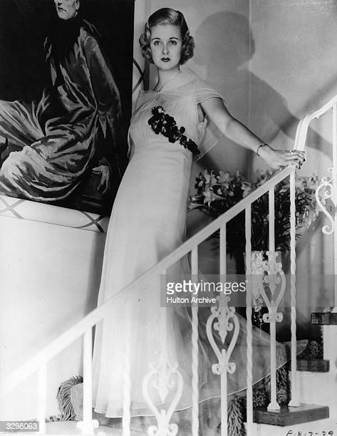 Joan Bennett the American leading lady of the 30's and 40's descending stairs wearing a light evening gown designed by Yvonne Carol of New York