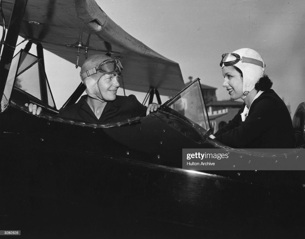 June Travis, the Warner Brothers starlet, taking flying lessons for her film 'Ceiling Zero', from Amelia Earhart (1898 - 1937), the American airwoman from Kansas who was the first woman to fly the Atlantic from Newfoundland to Wales in 1928.