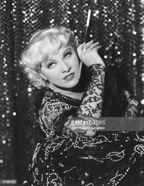 Mae West smoking from a cigarette holder.