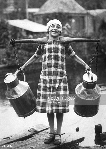 Marie Antoinette Harel the 12 yearold grand niece of the inventor of camembert cheese carrying two milk churns on a yoke