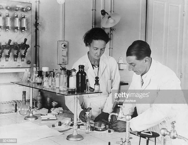 Married French physical chemists Irene Curie and Jean Frederic Joliot work on an experiment at a table in their laboratory at the Paris Radium...