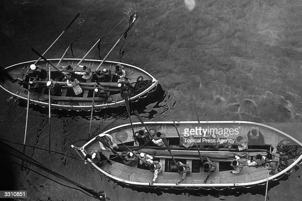 Members of the crew of the SS Madura leaving their ship during an 'abandon ship' safety drill
