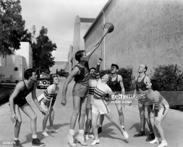 Members of the Motion Picture Studio All Stars Basketball Team the stars of Ray McCarey's short film 'Basketball' playing ball with four starlets on...