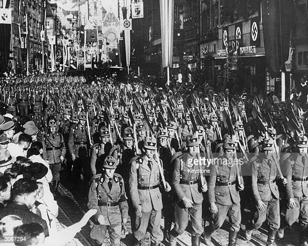Nazi soldiers parade through cheering crowds in pre-war Italy.