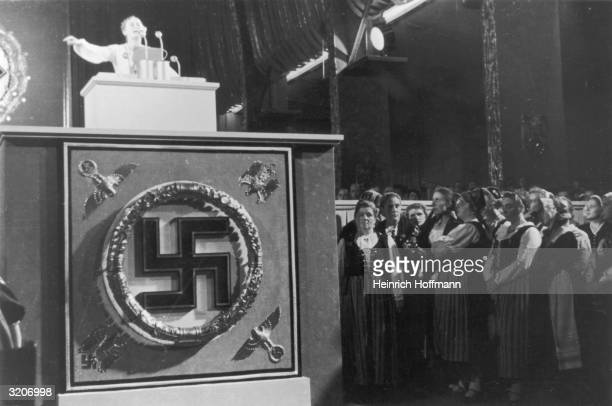 Nazi Women's League leader Gertrude ScholtzKlink speaks from a podium while a group of women in traditional German folk costumes watches from below...