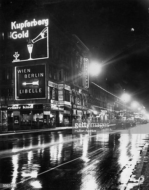 Neon adverts in a wet Berlin street at night