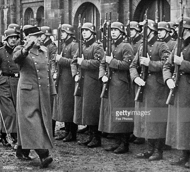 Norwegian diplomat and Fascist leader Vidkun Quisling inspects German troops in the Nazi style on a visit to Germany