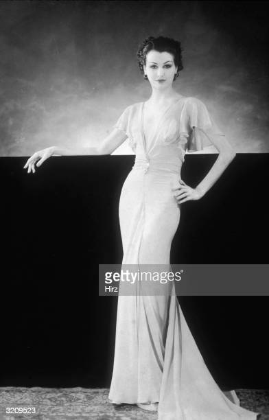 Portrait of a woman leaning on a wall while modelling a long chiffon dress with a plunging Vneck ruffled cap sleeves and a fishtail train