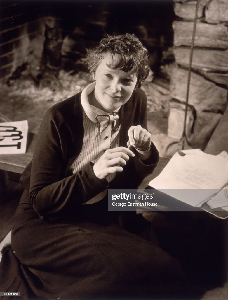 Portrait of American aviator Amelia Earhart (1898 - 1937) sitting before a pile of papers, holding a pencil and wearing a button-down dress.