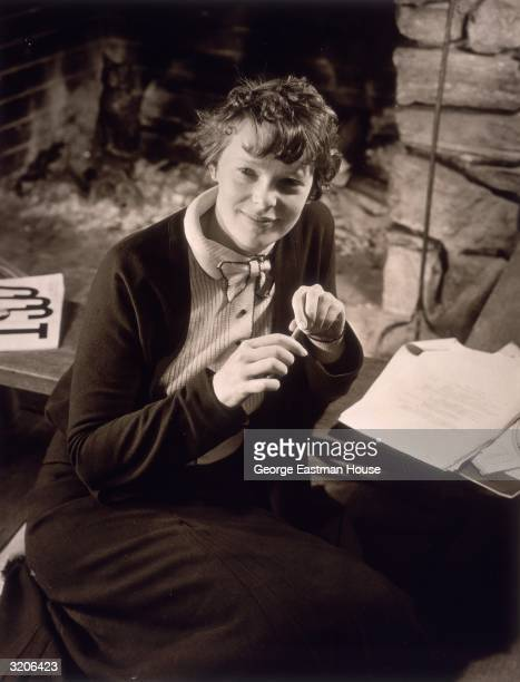 Portrait of American aviator Amelia Earhart sitting before a pile of papers holding a pencil and wearing a buttondown dress